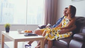 Jong mooi paar die op TV letten bij woonkamer in flat door het panoramische venster royalty-vrije stock foto