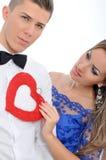 Jong mooi paar die rood hart samen houden Royalty-vrije Stock Afbeeldingen