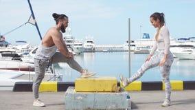 Jong mooi paar die uitrekkende oefeningen doen bij de oceaanpijler stock footage