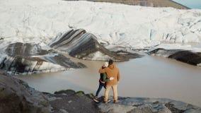 Jong mooi paar die zich op de kust van het meer in Vatnajokull-ijslagune bevinden in IJsland en op gletsjers kijken stock videobeelden