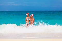 Jong mooi paar in liefde die pret in golven geklede I hebben Royalty-vrije Stock Fotografie