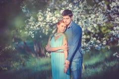 Jong mooi paar in liefde onder appelbomen Royalty-vrije Stock Foto's