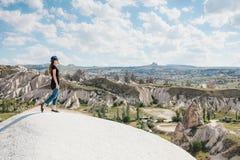 Jong mooi reismeisje bovenop een heuvel in Cappadocia, Turkije Reis, succes, vrijheid, voltooiing royalty-vrije stock afbeelding