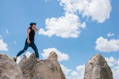 Jong mooi reismeisje bovenop een heuvel in Cappadocia, Turkije Reis, succes, vrijheid, voltooiing Zij gaat stock afbeelding