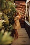 Jong mooi rijk meisje in het gele kleding stellen bij palm stock fotografie