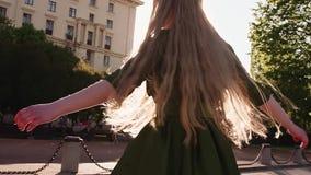 Jong mooi roodharigemeisje in het groene kleding spinnen bij stadsvierkant stock footage