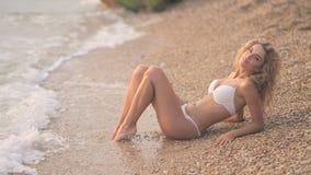 Jong mooi sexy gelooid meisje in bikini met blond haar die op het strand bij zonsondergang op de overzeese kust liggen stock footage