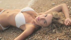 Jong mooi sexy gelooid meisje in bikini met blond haar die op het strand bij zonsondergang op de overzeese kust liggen stock video
