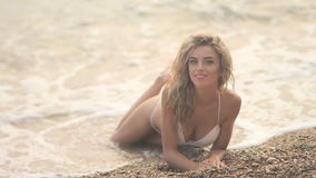 Jong mooi sexy gelooid meisje in bikini met blond haar die op het strand bij zonsondergang op de overzeese kust liggen stock videobeelden