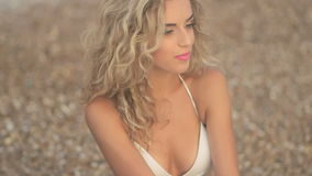 Jong mooi sexy gelooid meisje in bikini met blonde haarzitting op het strand bij zonsondergang op de overzeese kust stock video