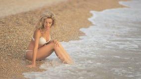Jong mooi sexy gelooid meisje in bikini met blonde haarzitting op het strand bij zonsondergang op de overzeese kust stock footage