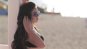 Jong mooi sexy meisje in bikini die en in strandbar bij zonsondergang stellen dansen stock videobeelden