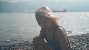 Jong mooi sexy meisje in een badpakzitting op een rotsachtige kust Het blonde in een zwempak zit op de kust stock footage