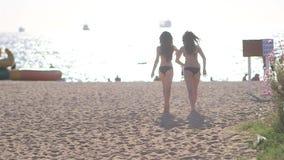 Jong mooi sexy meisje twee in een bikini die op het strand tijdens zonsondergang lopen stock video