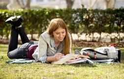 Jong mooi studentenmeisje die op het gras van het campuspark met boeken gelukkig het voorbereidingen treffen examen in onderwijsc Stock Afbeelding