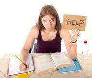 Jong mooi studentmeisje die voor universitair examen in spanning bestuderen die om hulp onder testdruk vragen Stock Foto