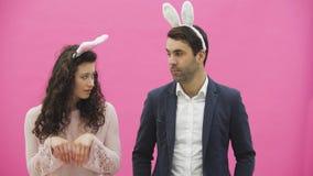 Jong mooi, teder creatief paar die zich op een roze achtergrond bevinden Tegelijkertijd, toont het voor de gek houden de beweging stock video