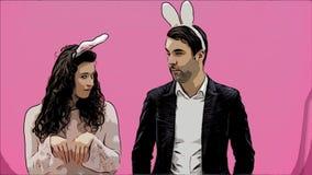 Jong mooi, teder creatief paar die zich op een roze achtergrond bevinden Tegelijkertijd, toont het voor de gek houden de beweging stock videobeelden