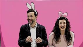 Jong mooi, teder creatief paar die zich op een roze achtergrond bevinden Tegelijkertijd, toont het voor de gek houden de beweging stock footage