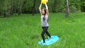 Jong mooi tienermeisje die in grijze mouwloos onderhemd het praktizeren geschiktheid, in park in de zomerdag in openlucht uitoefe stock footage