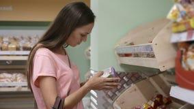 Jong mooi vrouw het kopen knäckebrood in een supermarkt stock video