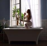 Jong mooi vrouwen drinkwater dichtbij badkuipbad en open badkamersvenster stock afbeeldingen