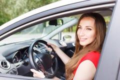 Jong mooi vrouwenstuurwiel die een auto drijven Stock Foto