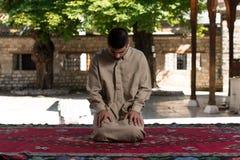 Jong Moslimguy praying stock afbeeldingen