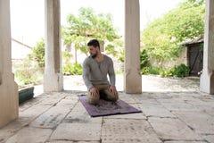 Jong Moslimguy praying stock afbeelding