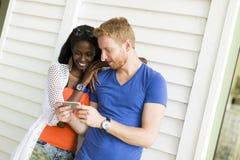 Jong multi-etnisch paar met smartphone bij de zomer royalty-vrije stock foto