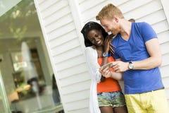 Jong multi-etnisch paar met smartphone bij de zomer stock foto's
