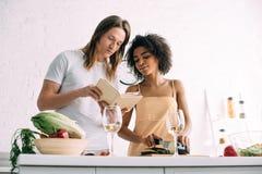 jong multicultureel paar die recept in boek bekijken stock foto