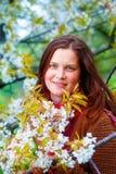 Jong natuurlijk meisje met kersenbloesem in de lentelandschap royalty-vrije stock afbeelding