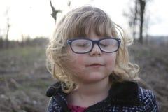 Jong nerdy meisje met glazen op de leeftijd van 3-5, blondehaar, blauwe ogen Kleuterportretten stock afbeelding