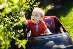 Jong nieuwsgierig jong geitje met stuk speelgoed auto in openlucht royalty-vrije stock foto's