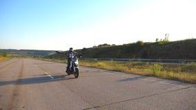 Jong onbezorgd personenvervoer op een motor zonder handen De motorrijder die zijn motorfiets op de weg drijven en geeft vrij stock footage