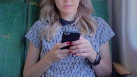 Jong onherkenbaar meisje met mooie rode spijkers, die in de zetel van een vliegtuig, een trein of een bus zitten Gebruikt mobiel stock video
