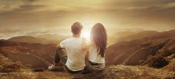 Jong, ontspannen paar die op een zonsondergang letten Royalty-vrije Stock Foto