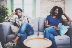 Jong ontstemd zwart paar Amerikaanse Afrikaanse mensen die met zijn modieus meisje debatteren, dat op bank op laag zit Stock Foto's