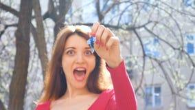 Jong opgewekt meisje die sleutel van nieuwe onroerende goederen met blauwe keychain, vrouwelijke hand met de rode sleutels van de stock video