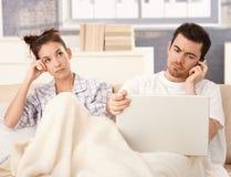 Jong paar in bedman werkende bored vrouw stock foto