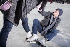 Jong paar bij ijsbaan, vrouw die de mens omhoog na het vallen helpen stock afbeelding