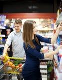 Jong paar dat bij supermarkt winkelt Stock Foto's