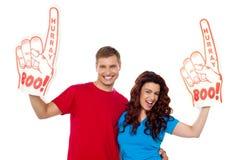 Jong paar dat boe-geroep hurray schuimhand toont Stock Fotografie