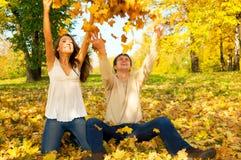 Jong paar dat de herfstbladeren werpt Stock Foto's
