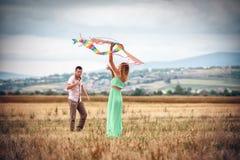 Jong paar dat een vlieger vliegt royalty-vrije stock fotografie