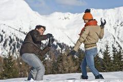 Jong paar dat foto's op de sneeuw neemt Stock Fotografie