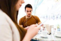 Jong paar dat hun mobiele telefoons met behulp van terwijl het zitten bij koffie stock foto