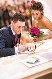 Jong paar dat huwelijksdocumenten ondertekent Stock Fotografie