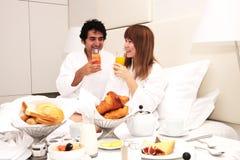 Jong paar dat ontbijt in bed heeft Stock Afbeelding